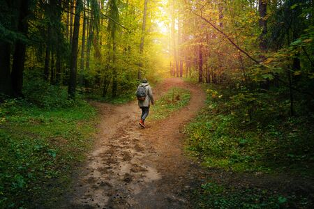 A man with backpack walks in the amazing autumn forest. Hiking alone along autumn forest paths. Travel concept. 版權商用圖片 - 132622488