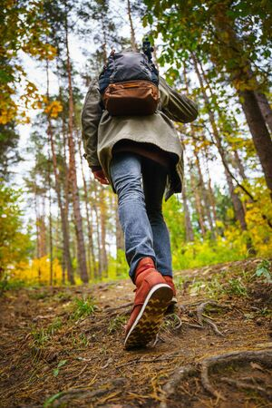 Nature photographer with a tripod on his shoulder and backpack climbs the slopein the amazing autumn forest. Hiking alone along autumn forest paths. Travel concept. 版權商用圖片 - 132622902