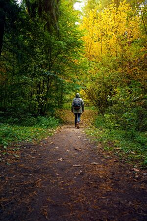 A man with backpack walks in the amazing autumn forest. Hiking alone along autumn forest paths. Travel concept. Foto de archivo - 133743911