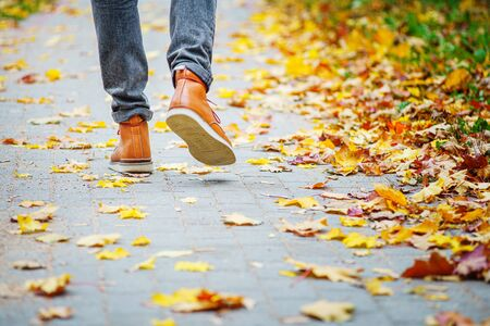 Back view on the feet of a man in brown boots walking along the sidewalk strewn with fallen leaves. The concept of turnover of the seasons of the year. Weather background