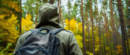 A man with backpack walks in the amazing autumn forest. Hiking alone along autumn forest paths. Travel concept. 版權商用圖片 - 132623968