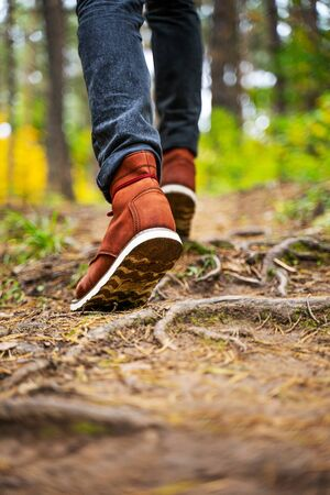 A man in red leather boots walks in the amazing autumn forest. Footwear close up with copy spase. Travel concept. 版權商用圖片 - 132623787