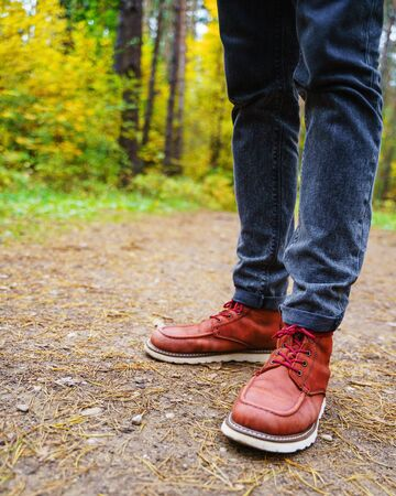 A man in red leather boots walks in the amazing autumn forest. Footwear close up with copy spase. Travel concept. 版權商用圖片 - 132623990