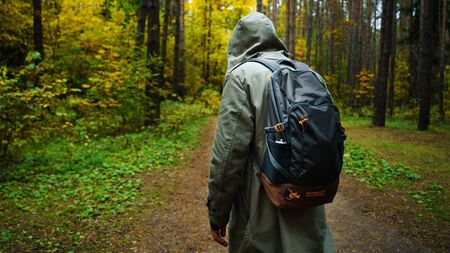 A man with backpack walks in the amazing autumn forest. Hiking alone along autumn forest paths. Travel concept. 版權商用圖片 - 132624416