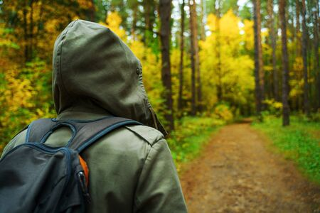 A man with backpack walks in the amazing autumn forest. Hiking alone along autumn forest paths. Travel concept. 版權商用圖片 - 132624256