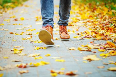 legs of a man in brown boots walking along the sidewalk strewn with fallen leaves. The concept of turnover of the seasons of the year. Weather background 版權商用圖片 - 132624843