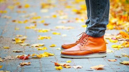 legs of a man in brown boots on the sidewalk strewn with fallen leaves. The concept of turnover of the seasons of the year. Weather background
