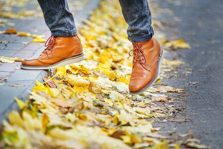 legs of a man in brown boots walking along the sidewalk strewn with fallen leaves. The concept of turnover of the seasons of the year. Weather background 版權商用圖片 - 132625543