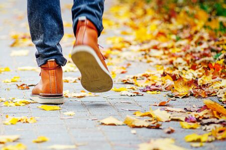 Back view on the feet of a man in brown boots walking along the sidewalk strewn with fallen leaves. The concept of turnover of the seasons of the year. Weather background 版權商用圖片 - 132623941