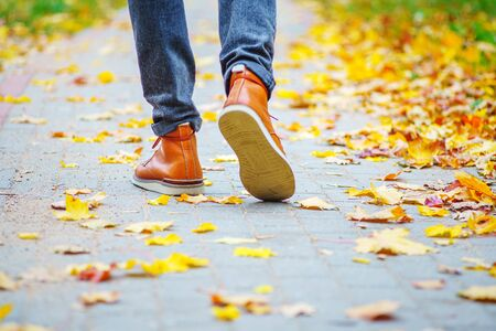 Back view on the feet of a man in brown boots walking along the sidewalk strewn with fallen leaves. The concept of turnover of the seasons of the year. Weather background 版權商用圖片 - 132625562