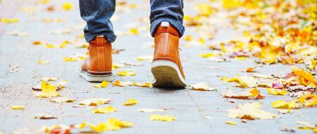 Back view on the feet of a man in brown boots walking along the sidewalk strewn with fallen leaves. The concept of turnover of the seasons of the year. Weather background 版權商用圖片 - 132624352