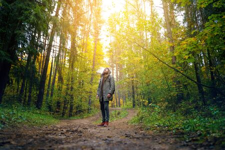 A man with backpack walks in the amazing autumn forest. Hiking alone along autumn forest paths. Travel concept. 版權商用圖片 - 132624689
