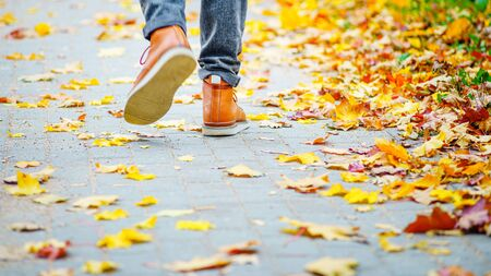 Back view on the feet of a man in brown boots walking along the sidewalk strewn with fallen leaves. The concept of turnover of the seasons of the year. Weather background 版權商用圖片 - 132624185