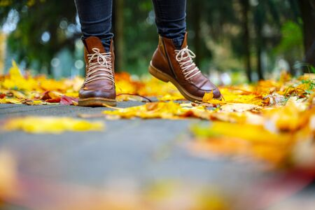 legs of a woman in black pants and brown boots walking in a park along the sidewalk strewn with fallen leaves. The concept of turnover seasons. Weather background 版權商用圖片 - 132624663