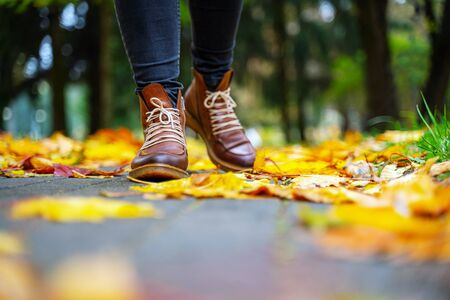 legs of a woman in black pants and brown boots walking in a park along the sidewalk strewn with fallen leaves. The concept of turnover seasons. Weather background 版權商用圖片 - 132625630