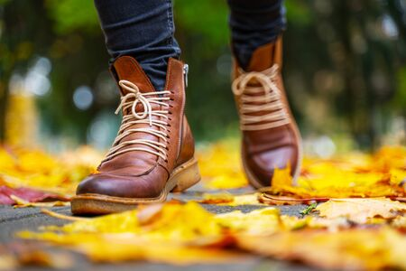 legs of a woman in black pants and brown boots walking in a park along the sidewalk strewn with fallen leaves. The concept of turnover seasons. Weather background 版權商用圖片 - 132624448