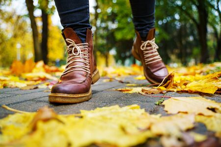 legs of a woman in black pants and brown boots walking in a park along the sidewalk strewn with fallen leaves. The concept of turnover seasons. Weather background 版權商用圖片 - 132624358