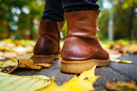 legs of a woman in black pants and brown boots walking in a park along the sidewalk strewn with fallen leaves. The concept of turnover seasons. Weather background 版權商用圖片 - 132625132
