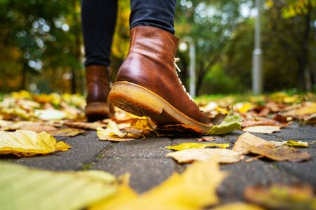 Back view on the feet of a woman in black pants and brown boots walking in a park along the sidewalk strewn with fallen leaves. The concept of turnover seasons. Weather background 版權商用圖片 - 132630132