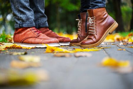 Feet of a couple in love in brown shoes on the path of the autumn park, strewn with fallen leaves. Girl stands on toes. Kiss concept 版權商用圖片 - 132626155