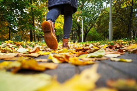 legs of a woman in black pants and brown boots walking in a park along the sidewalk strewn with fallen leaves. The concept of turnover seasons. Weather background 版權商用圖片 - 132633854