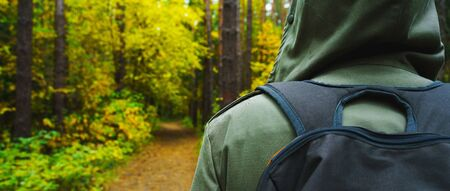 A man with backpack walks in the amazing autumn forest. Hiking alone along autumn forest paths. Travel concept. 版權商用圖片 - 132631106