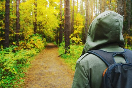 A man with backpack walks in the amazing autumn forest. Hiking alone along autumn forest paths. Travel concept. 版權商用圖片 - 132631188