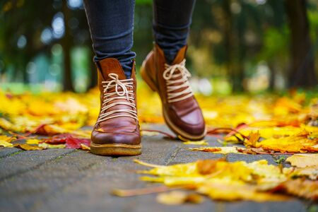 legs of a woman in black pants and brown boots walking in a park along the sidewalk strewn with fallen leaves. The concept of turnover seasons. Weather background 版權商用圖片 - 132626867