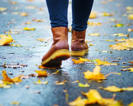Walk on wet sidewalk. Back view on the feet of a woman walking along the asphalt pavement with puddles in the rain. Pair of shoe on slippery road in the fall. Abstract empty blank of the autumn weathe 版權商用圖片 - 132624839