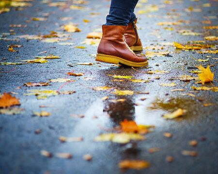 Walk on wet sidewalk. Back view on the feet of a woman walking along the asphalt pavement with puddles in the rain. Pair of shoe on slippery road in the fall. Abstract empty blank of the autumn weathe 版權商用圖片 - 132626419