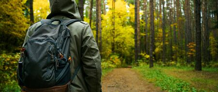A man with backpack walks in the amazing autumn forest. Hiking alone along autumn forest paths. Travel concept. 版權商用圖片 - 132631077