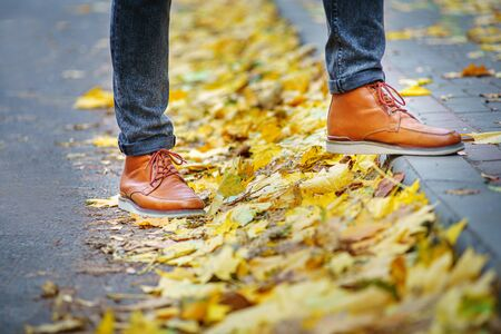 legs of a man in brown boots walking along the sidewalk strewn with fallen leaves. The concept of turnover of the seasons of the year. Weather background 版權商用圖片 - 132629707