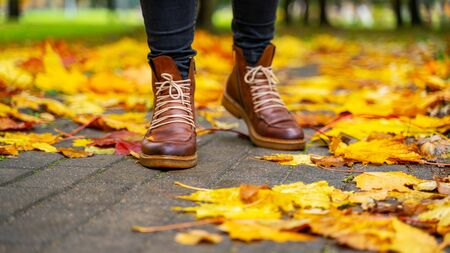 legs of a woman in black pants and brown boots walking in a park along the sidewalk strewn with fallen leaves. The concept of turnover seasons. Weather background 版權商用圖片 - 132626281