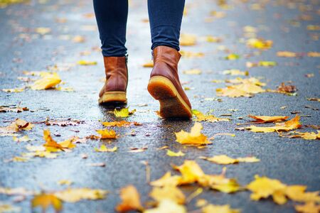 Walk on wet sidewalk. Back view on the feet of a woman walking along the asphalt pavement with puddles in the rain. Pair of shoe on slippery road in the fall. Abstract empty blank of the autumn weathe 版權商用圖片 - 132626575
