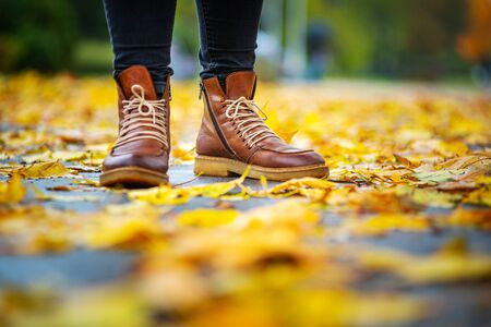 legs of a woman in black pants and brown boots in autumn park on sidewalk strewn with fallen leaves. The concept of turnover seasons. Weather background 版權商用圖片 - 132635543