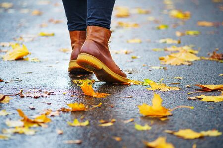 Walk on wet sidewalk. Back view on the feet of a woman walking along the asphalt pavement with puddles in the rain. Pair of shoe on slippery road in the fall. Abstract empty blank of the autumn weathe 版權商用圖片 - 132627126