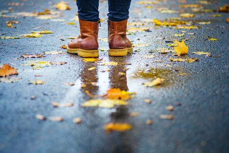 Walk on wet sidewalk. Back view on the feet of a woman standing on the asphalt pavement with puddles in the rain. Pair of shoes on slippery road in the fall. Abstract empty blank of the autumn weathe 版權商用圖片 - 132632375