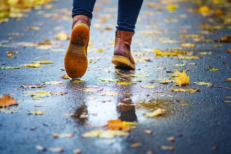 Walk on wet sidewalk. Back view on the feet of a woman walking along the asphalt pavement with puddles in the rain. Pair of shoe on slippery road in the fall. Abstract empty blank of the autumn weathe 版權商用圖片 - 132629851