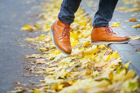 legs of a man in brown boots walking along the sidewalk strewn with fallen leaves. The concept of turnover of the seasons of the year. Weather background 版權商用圖片 - 132631543