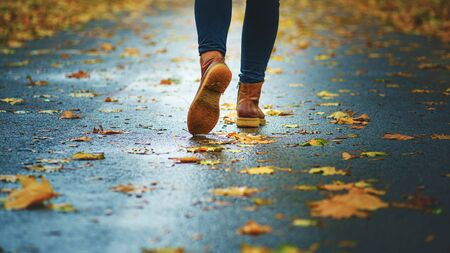 Walk on wet sidewalk. Back view on the feet of a woman walking along the asphalt pavement with puddles in the rain. Pair of shoe on slippery road in the fall. Abstract empty blank of the autumn weathe 版權商用圖片 - 132626456