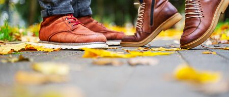 Feet of a couple in love in brown shoes on the path of the autumn park, strewn with fallen leaves. Girl stands on toes. Kiss concept 版權商用圖片