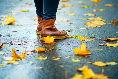 Walk on wet sidewalk. Back view on the feet of a woman standing on the asphalt pavement with puddles in the rain. Pair of shoes on slippery road in the fall. Abstract empty blank of the autumn weathe 版權商用圖片 - 132630004