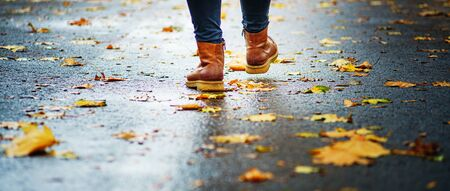 Walk on wet sidewalk. Back view on the feet of a woman walking along the asphalt pavement with puddles in the rain. Pair of shoe on slippery road in the fall. Abstract empty blank of the autumn weathe 版權商用圖片 - 132631963