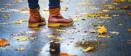 Walk on wet sidewalk. Back view on the feet of a woman standing on the asphalt pavement with puddles in the rain. Pair of shoes on slippery road in the fall. Abstract empty blank of the autumn weathe 版權商用圖片 - 132631914