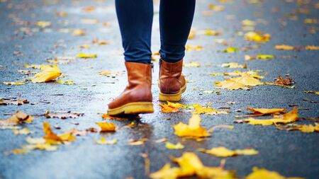 Walk on wet sidewalk. Back view on the feet of a woman walking along the asphalt pavement with puddles in the rain. Pair of shoe on slippery road in the fall. Abstract empty blank of the autumn weathe 版權商用圖片 - 132632253