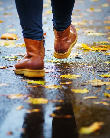 Walk on wet sidewalk. Back view on the feet of a woman walking along the asphalt pavement with puddles in the rain. Pair of shoe on slippery road in the fall. Abstract empty blank of the autumn weathe 版權商用圖片
