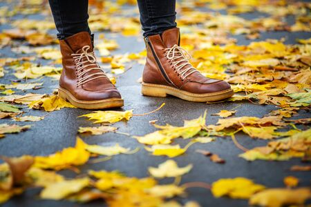 legs of a woman in black pants and brown boots in autumn park on sidewalk strewn with fallen leaves. The concept of turnover seasons. Weather background 版權商用圖片 - 132629757