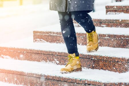 A young woman in yellow leather boots descends on snowy granite steps in an urban environment. Winter walk. Abstract winter weather background Archivio Fotografico