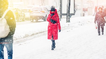 A young woman in a red coat wraps herself and hides from the wind. Snowstorm in an urban environment. Abstract winter weather background Stok Fotoğraf