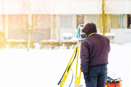 Surveyor engineer uses a total station at a construction site. Geodetic works. Building construction